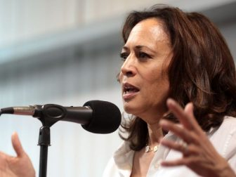 Kamala Harris speaking into microphone