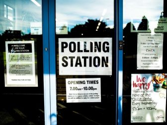 Polling station sign on a glass door