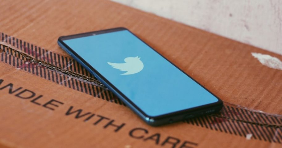 Twitter loading screen on a smartphone sitting on a cardboard box.