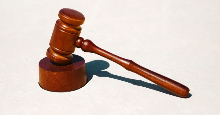 Brown wooden gavel on white surface