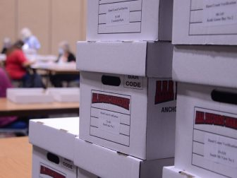 Boxes of ballots are seen stacked for hand counting in Juneau, Alaska's Centennial Hall following Alaska's Aug. 18, 2020 statewide primary. (James Brooks photo)
