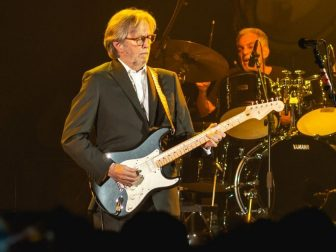Eric Clapton playing guitar in concert