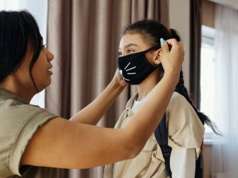 Mother putting face mask on her daughter