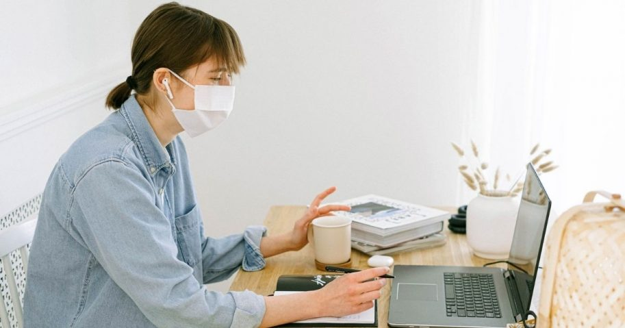 Woman wearing face mask while working from home