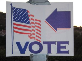The above stock image shows a sign pointing to where people can go vote.