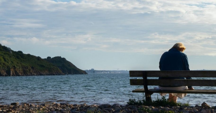 Woman sitting on a wooden bench overlooking a shoreline