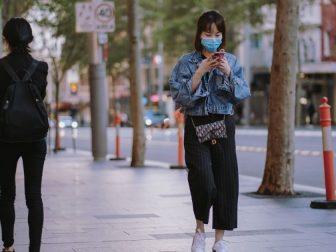 Woman in face mask walking down the street during a coronavirus lockdown