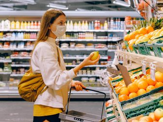 Woman in mask shopping at a fruit stand