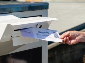 Everett, WA - USA / 07/30/2020: Dropping Mail in Ballot into mail box