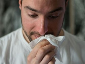 Man wiping nose with a tissue