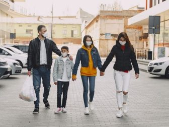 Family in medical masks walking along parking