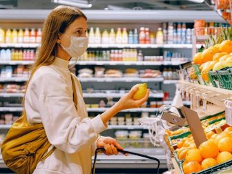 Woman in a yellow tshirt, beige jacket and mask picking out fruit.