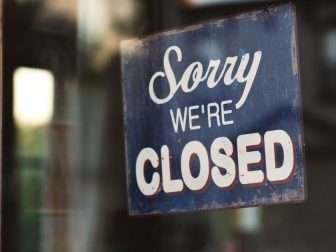 Closed sign hanging in window of storefront