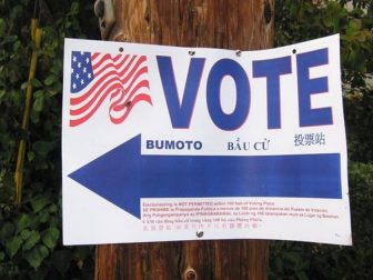 "A ""Vote"" sign is seen above."