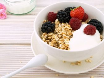 A bowl of yogurt with granola and fresh berries