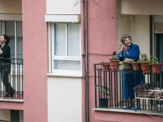 People standing on apartment balconies in lockdown.