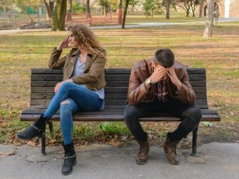 Frustrated man and woman sitting on a park bench