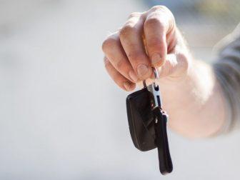 Person in grey shirt handing in keys