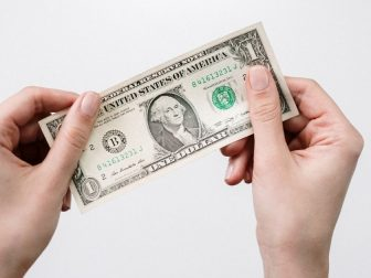 Hands holding a US dollar bill