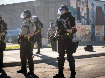Police officers standing guard towards George Floyd protestors in minneapolis riots