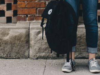 Student standing against a brick wall with a backpack in hand