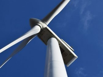 Looking up at a wind turbine against a blue sky