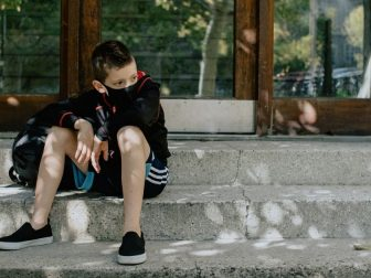 boy with mask on on the steps waiting for school