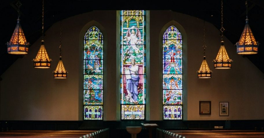 Church sanctuary with pews and stained glass windows