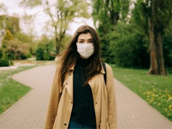 Girl walking through park in a mask