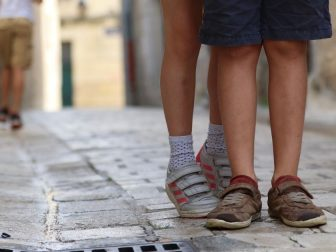 Shoes of a young boy and girl on a road.