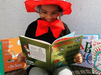 Girl reading Dr. Suess books