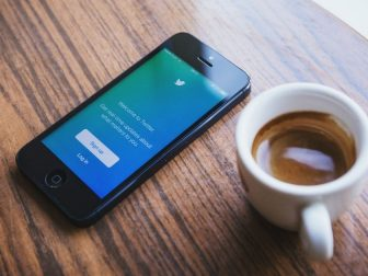 Twitter login screen on a phone sitting next to a cup of espresso