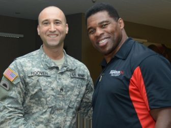 Herschel Walker shaking hands with a member of the National Guard
