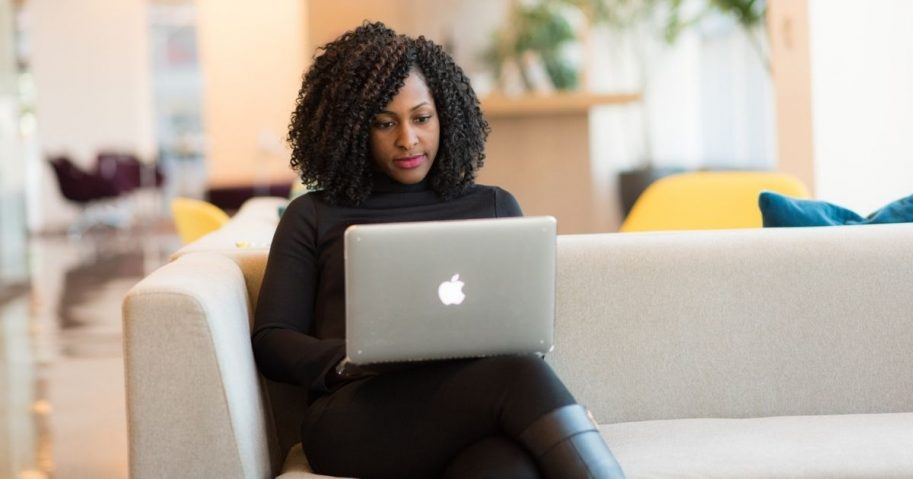 Woman on a Macbook sitting on a white couch