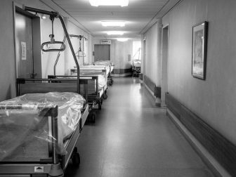 Hospital beds lined up in a hallway