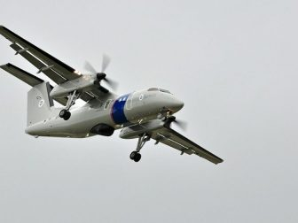 """The CBP Dash 8 comes in for a landing after being part of the """"air showcase"""" at EAA AirVenture 2011."""