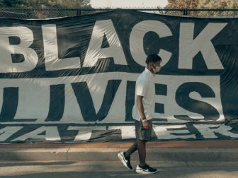 Man walks in front of a Black Lives Matter flag