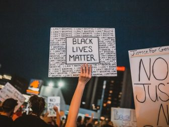 Rioters holding BLM and justice signs