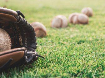 Baseballs and baseball mitt on grass