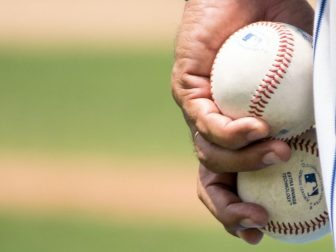 Man's hand holding two basballs