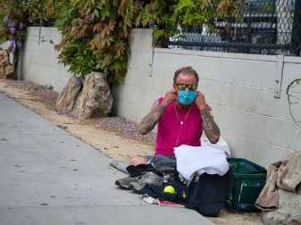 A homeless man puts on his face mask during the COIVD outbreak.