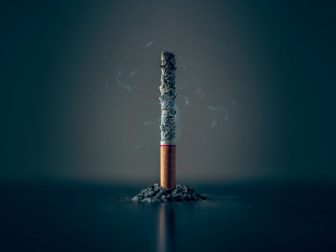 Burning cigarette against a dark background