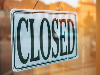Closed sign hanging in a storefront