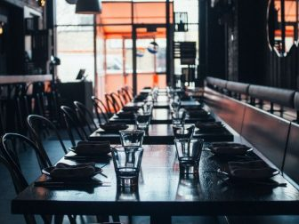 Set tables in a closed and darkened restaurant.