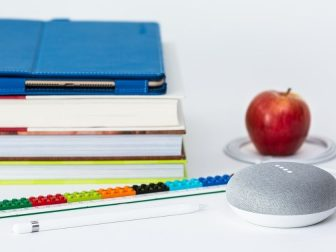 A stack of school books, an iPad Pro in a saturated blue Snugg case, an Apple Pencil, a multicolored Lego ruler, a Google Home Mini processing a command, and a red apple encircled by the Google Home power cord.
