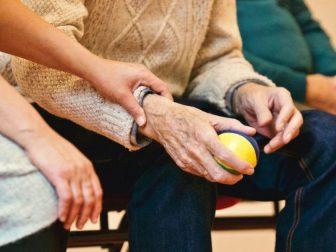 An elderly person holding a stress ball