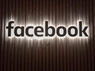 Facebook sign on a wood-paneled wall