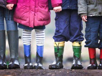 Four kids wearing muddy rain boots