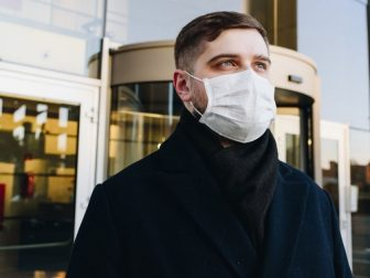 Man, young professional, outside his office during coronavirus COVID-19 outbreak and pandemic wearing a face mask