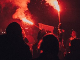 Hooded people holding roman candles at a night riot.